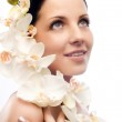 The beautiful young woman with flowers — Stock Photo
