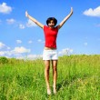Happy young woman jumping in a field - Stock Photo
