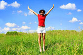 Happy young woman jumping in a field — Stock Photo