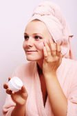 Young woman applying creme on face — Stock Photo