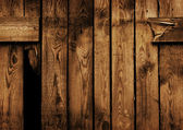Old brown wood fence with a hole — Stockfoto