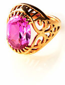 Golden ring with pink gem over white — Stock Photo