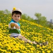 Boy sits on a grass — Stockfoto