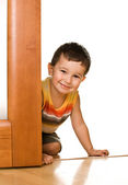 Boy peeks out from a door — Stockfoto