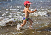 Happy boy running in water — Stock Photo
