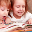Girl and boy friendly reading an interesting book — Stock Photo #1028801