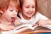 Girl and boy friendly reading an interesting book — Stock Photo