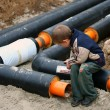 Child sitting on a pipe — Stock Photo #1024699