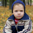 Serious boy in autumn — Stock Photo