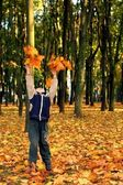 Child throwing autumn leaves — Stock Photo