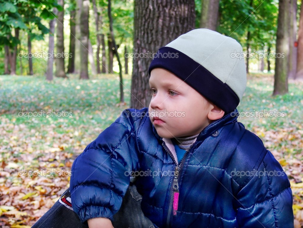 A little boy with an indifferent look sits on a bench in an autumn park. It is silence...  Stock Photo #1023503