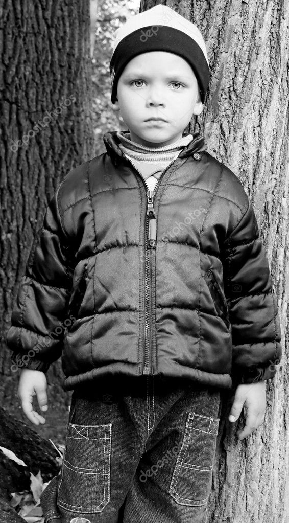 A little boy in an autumn park looks on you a serious look. It is serious... — Stock Photo #1023522