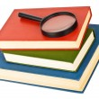 Stock Photo: Magnifying glass on pile of books