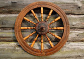 Spinning Wheel On The Log House Wall — Stock Photo