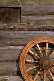Spinning Wheel On The Log Hut Wall — Stock Photo