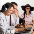 Office workers with laptops and a dog — Stock Photo