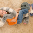 Two kids with a toy on the floor — Stock Photo #1024086