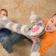 Two kids with a toy cat on the floor — Stock Photo