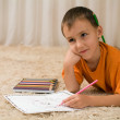 Young kid with pencils on the carpet. — Stock Photo