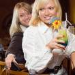 Royalty-Free Stock Photo: Two blonds at a bar counter with a cockt