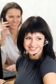 Young brunette with a headset in busines — Stock Photo