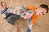 Two kids with a toy cat on the soft carp — Stock Photo