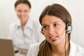 Young girl with headset in the office — Stock Photo