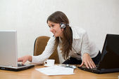 Young businesswoman at the desk with two — Stock Photo