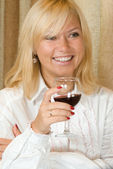 Smiling blond with a glass of red wine — Stock Photo
