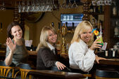 Three pretty girls at a bar counter — Stock Photo