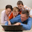 Family looking at laptop - Stock Photo