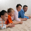 Family of four lying on the carpet — Stock Photo #1127903