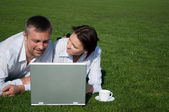A man and a girl with a laptop on the gr — Stock Photo