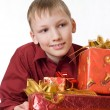 Happy boy in a red shirt with gifts — Stock Photo