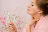 Elderly woman looks in the mirror — Stock Photo