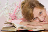 Elderly woman reading a book and dreams — Stock Photo