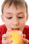 Child holding an apple and bites his — Stock Photo
