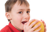Child in a red shirt holding an apple — Стоковое фото