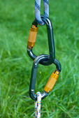 Carabiners on a green grass background — Stock Photo