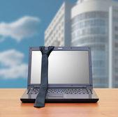 Laptop, tie in the office interior — Stock Photo