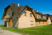 Big wooden house with straw roof — Stock Photo