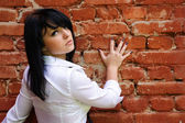 Vrouw in de buurt van de bakstenen muur — Stockfoto