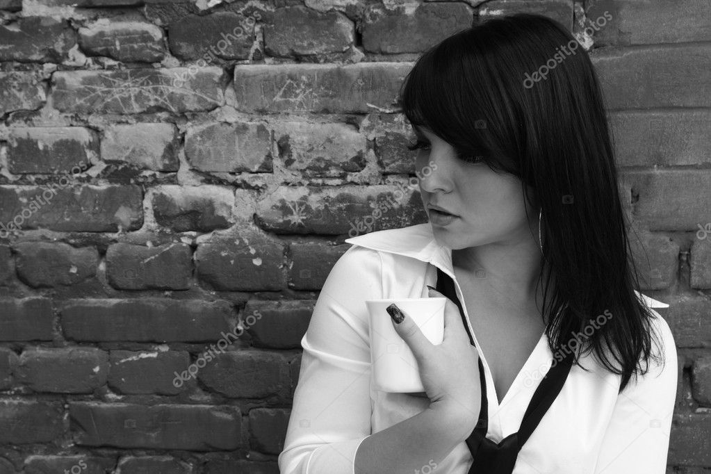 Woman with a cup on a background of a brick wall. black-and-white image — Stock Photo #1027917