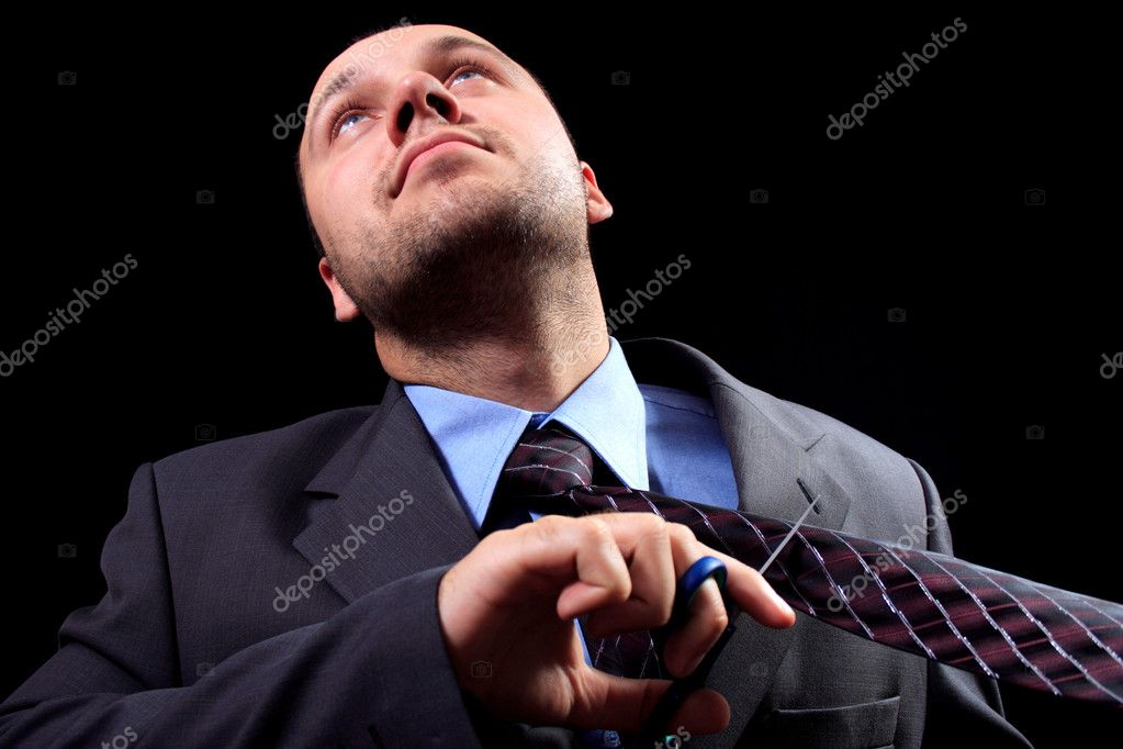 Man in a business suit scissors the tie, on a black background — Stock Photo #1028394