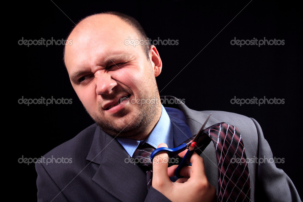 Man in a business suit scissors the tie, on a black background  Stock Photo #1028416