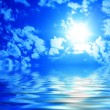Sun among clouds in the blue sky and reflection of the sky in water — Stock Photo #1035085