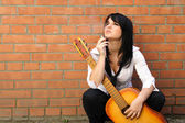 Woman with a cigarette and a guitar — Stock Photo