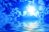 Sun among clouds in the blue sky and reflection of the sky in water — Stock Photo