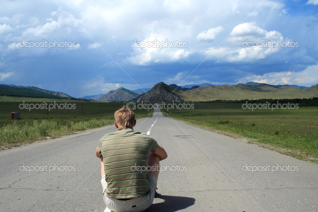 Man sits in the middle of road of the leader to mountains — Stock Photo #1030164