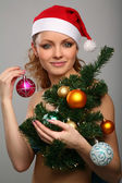 Girl with Christmas tree in the hands — Stock Photo